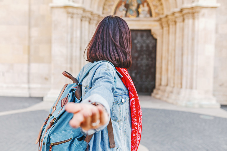 Follow me to Matthias church in Budapest. Mixed race woman traveler with backpack heading to tourist sights and destinations in Europe